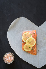 Salmon with lemon slices, thyme, pepper and Himalayan salt to bake in parchment