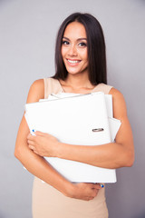 Happy businesswoman standing with folders
