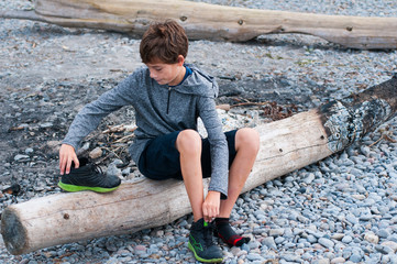 child sitting on a rocky beach putting on his shoes
