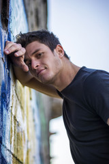 Attractive young man leaning against graffiti wall