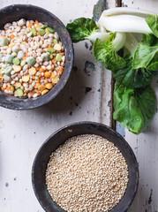 Quinoa Burger ingredients: quinoa, mangold, dry grain mix, chili pepper, eggs green peas basil on white rustic board