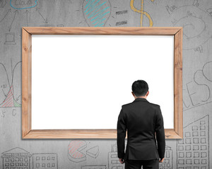 Businessman looking at wooden frame with blank white view