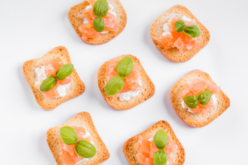 Top view on canapes with smoked salmon and cottage cheese.
