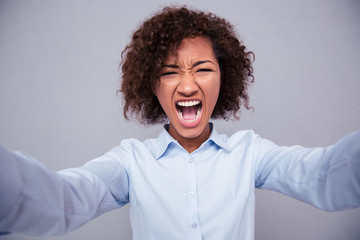 Afro american woman screaming and making selfie photo
