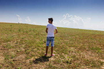 alone teenager standing on wide free grassland
