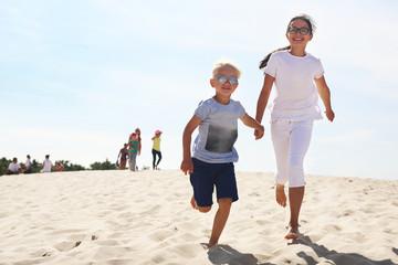 Słoneczne wakacje. Dzieci biegną po plaży