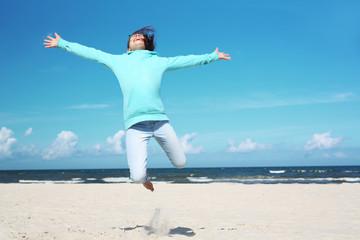 Wakacje! Dziewczynka wysoko podskakuje na piaszczystej plaży