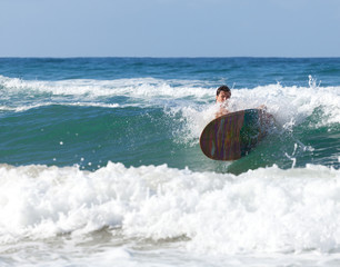 Surfer on longboard while it is falling in the waves
