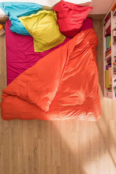 top view of an bed with a duvet and brightly colored pillows