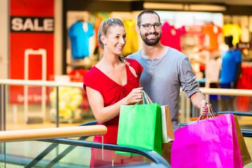 Mann und Frau vor Läden in Einkaufszentrum