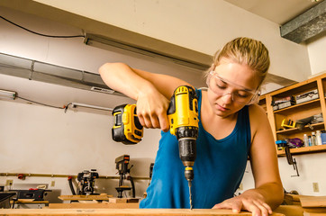 Caucasian young adult female woodworker using a power drill in workshop