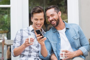 Happy homosexual couple looking at smartphone