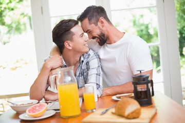 Happy homosexual couple looking at each other during breakfast