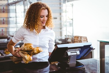 Pretty barista using cash register and holding loaf of bread