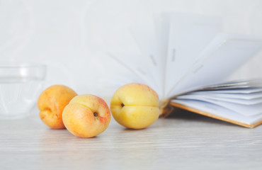 Three ripe apricots on background of open pages of book