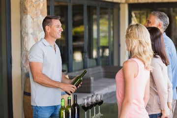 Smiling sommelier presents wine to customers