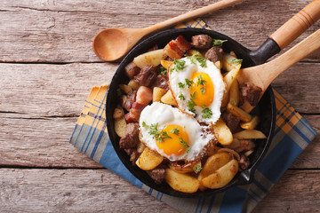 fried potatoes with meat, bacon and eggs in a pan. horizontal top view