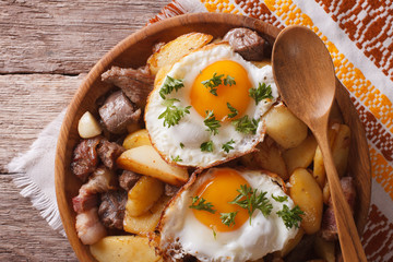 fried potatoes with meat and eggs close-up in a bowl. horizontal top view