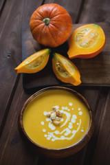 Pumpkin soup topped with pumpkin seeds and cream, studio shot