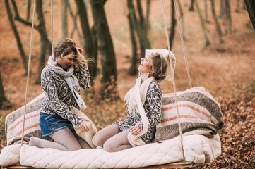 two beautiful twin sister on swing in autumn forest
