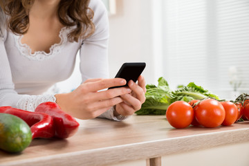 Woman Using Mobile Phone In Kitchen