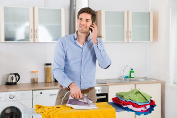 Man Talking On Mobile Phone While Ironing Clothes