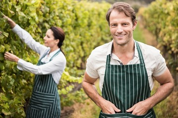 Happy winegrower couple working in the winery