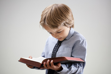 Child reading a book or bible