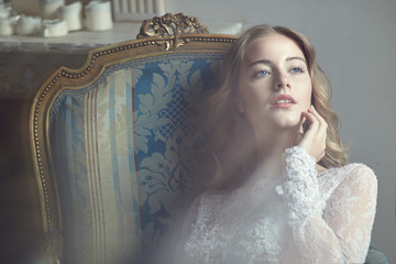 Model Bride in the studio sitting on a chair in the sunshine.