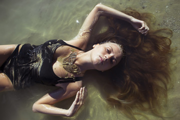 Young woman wearing butterfly-form necklace lying in water