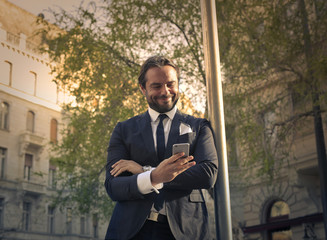 Happy businessman looking at his phone