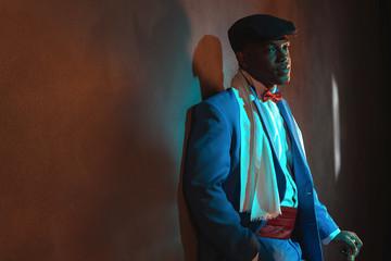 Retro african american man in blue suit wearing blue cap. Standi