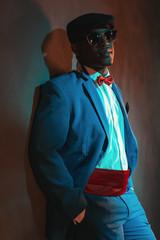 Retro african american man in blue suit wearing blue cap. Leanin
