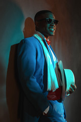 Retro african american man in blue suit wearing sunglasses. Lean