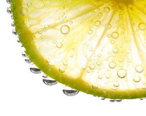 Slice of lime in the glass with gas water.