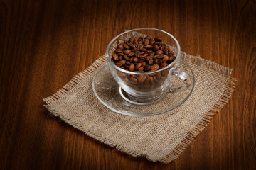 Cup with coffee beans on cloth burlap