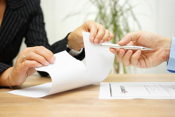 Woman tears agreement documents  in front of agent who wants to