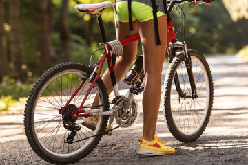 Rear view of mountain bike and woman's legs.
