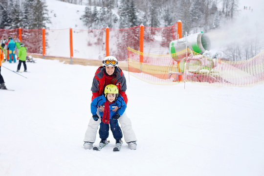 Beautiful young mom and her toddler boy, skiing in the mountains