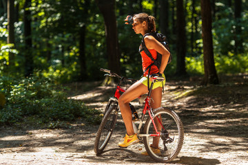 Woman riding a mountain bike in the forest.Making pause and looking around.