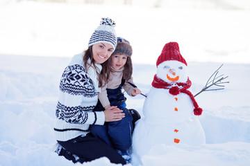 Happy beautiful family building snowman in garden, winter, mom a