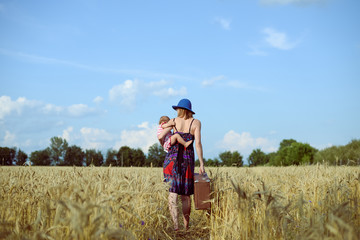 Woman wearing hat with baby-girl walking away on wheat field