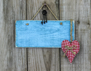 Blank blue sign with keys and hearts hanging on rustic wood background