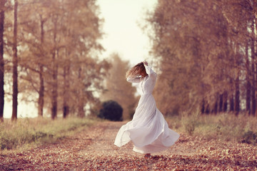 girl in white dress fall outside
