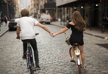 Lovers riding bicycle together holding hands