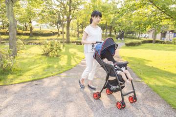 明るい公園でベビーカーを押す若いお母さん
