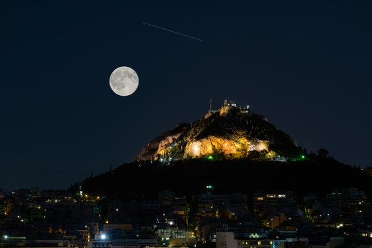 Lycabettus mountain in Athens Greece against the August full moon and a falling star.