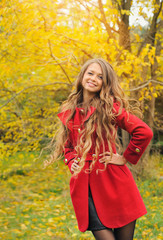 Fashion woman dressed in red coat in autumn park.