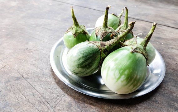 Round Green eggplants on dish on vintage wooden table