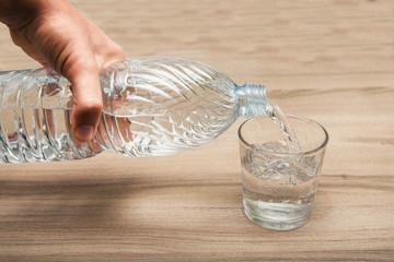 acqua nella bottiglia versata in un bicchiere trasparente